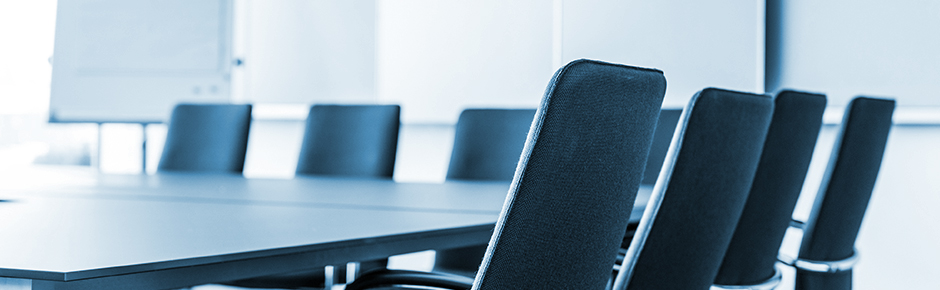 empty chairs around table in conference room